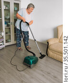 An elderly woman is engaged in cleaning the room with a vacuum cleaner. Стоковое фото, фотограф Владимир Ушаров / Фотобанк Лори