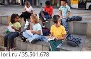 Multiethnic group of schoolchildren sitting with workbooks in schoolyard in warm autumn day. Стоковое видео, видеограф Яков Филимонов / Фотобанк Лори