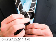 Junger Mann im Anzug bindet eine Krawatte. Стоковое фото, фотограф Zoonar.com/Robert Kneschke / age Fotostock / Фотобанк Лори