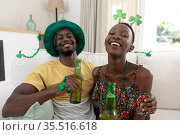 African american couple wearing st patrick's day costumes laughing and holding glasses of beer. Стоковое фото, агентство Wavebreak Media / Фотобанк Лори