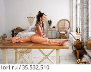 Young happy woman doing yoga sitting down in a split position at home. Стоковое фото, фотограф Алексей Кузнецов / Фотобанк Лори