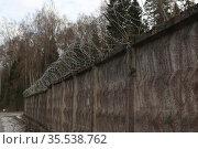Бетонный забор с колючей проволокой (егозой), ранняя весна. Стоковое фото, фотограф Цветкова Елена / Фотобанк Лори