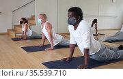 People in protective masks practice yoga in the gym. Стоковое видео, видеограф Яков Филимонов / Фотобанк Лори