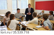 Male teacher standing at whiteboard in classroom, conducting lesson with teen students. Стоковое видео, видеограф Яков Филимонов / Фотобанк Лори