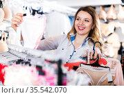 Female customer deciding on pretty clothing. Стоковое фото, фотограф Яков Филимонов / Фотобанк Лори