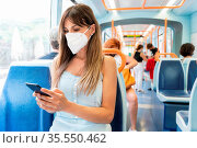 Young Woman Wearing a Face Mask Riding Public Transport. High quality... Стоковое фото, фотограф Zoonar.com/DAVID HERRAEZ CALZADA / easy Fotostock / Фотобанк Лори