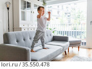 Cute child at home on sofa in the living room. Стоковое фото, фотограф Zoonar.com/Tomas Anderson / easy Fotostock / Фотобанк Лори