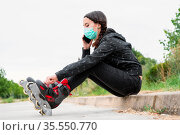 Woman in protective face mask on roller skating pause, sitting on... Стоковое фото, фотограф Zoonar.com/DAVID HERRAEZ CALZADA / easy Fotostock / Фотобанк Лори