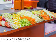Fresh raw chopped chopped grated vegetables and fruits tomato radish onion cabbage cucumber carrots potatoes lemon orange on the table, the concept of proper healthy nutrition and vegetarianism. Стоковое фото, фотограф Светлана Евграфова / Фотобанк Лори