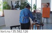 A woman paint artist drawing on a canvas with blue paint. Стоковое видео, видеограф Константин Шишкин / Фотобанк Лори