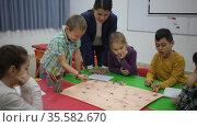 Happy kids and female teacher playing together educational board game in classroom at elementary school. Стоковое видео, видеограф Яков Филимонов / Фотобанк Лори