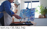 A woman paint artist drawing an abstract blue painting with brushes and palette knife. Стоковое видео, видеограф Константин Шишкин / Фотобанк Лори