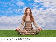 Young woman sitting in meditation pose on heavenly background. Стоковое фото, фотограф Евгений Харитонов / Фотобанк Лори