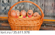 Stack of eggs with hand drawn faces on straw basket with colorful candy, easter preparation, holiday mood concepts. Стоковое фото, фотограф Ольга Балынская / Фотобанк Лори