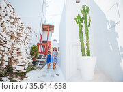 Family vacation in Europe. Father and kids at street of typical greek traditional village on Mykonos Island, in Greece. Стоковое фото, фотограф Дмитрий Травников / Фотобанк Лори