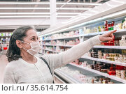 Senior woman wearing face mask shopping in supermarket. Стоковое фото, фотограф Дарья Филимонова / Фотобанк Лори