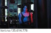 Tattooed woman puts on boxer gloves in neon lighting. Стоковое видео, видеограф Константин Шишкин / Фотобанк Лори