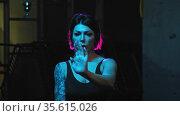 A strong tattooed woman showing karate moves in neon lighting. Стоковое видео, видеограф Константин Шишкин / Фотобанк Лори