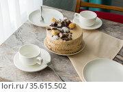 Сервированный к чаепитию стол: чайные чашки с блюдцами и бисквитный торт с масляным кремом на столешнице. Стоковое фото, фотограф Наталья Гармашева / Фотобанк Лори