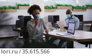 Diverse male and female business colleagues in face masks, woman talking on smartphone in office. Стоковое видео, агентство Wavebreak Media / Фотобанк Лори