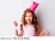 Happy laughing princess girl in crown and pink dress with lollipop... Стоковое фото, фотограф Zoonar.com/Ivan Mikhaylov / easy Fotostock / Фотобанк Лори