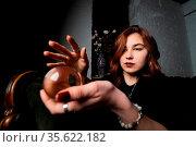 Woman in black suit holding crystal ball in her hands. Стоковое фото, фотограф Zoonar.com/Oleksii Hrecheniuk / easy Fotostock / Фотобанк Лори