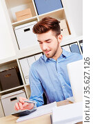Junger Geschäftsmann im Büro rechnet mit dem Taschenrechner eine ... Стоковое фото, фотограф Zoonar.com/Robert Kneschke / age Fotostock / Фотобанк Лори
