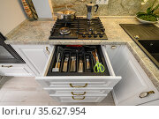 Drawers pulled out at modern classic white kitchen furniture. Стоковое фото, фотограф Сергей Старуш / Фотобанк Лори