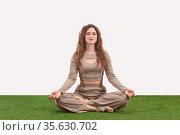 Young woman sitting in meditation pose on light background. Стоковое фото, фотограф Евгений Харитонов / Фотобанк Лори