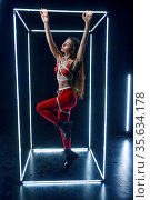 Stripper in bdsm lingerie dancing in luminous cube. Стоковое фото, фотограф Tryapitsyn Sergiy / Фотобанк Лори