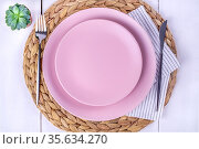 Two pink plates, a knife and a fork on a straw eco-friendly napkin. Стоковое фото, фотограф Ольга Губская / Фотобанк Лори