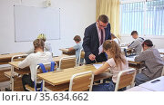Friendly teacher man helping students during lesson in schoolroom. Стоковое видео, видеограф Яков Филимонов / Фотобанк Лори