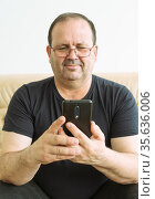The man is holding a smart phone and smiling. Стоковое фото, фотограф Владимир Ушаров / Фотобанк Лори