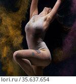 Gymnast in ecru bodysuit with colored dust around. Стоковое фото, фотограф Гурьянов Андрей / Фотобанк Лори