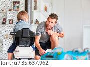 Vater spielt mit seinem Sohn auf dem Rutschauto zu Hause im Wohnzimmer. Стоковое фото, фотограф Zoonar.com/Robert Kneschke / age Fotostock / Фотобанк Лори