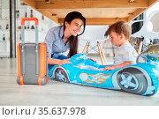Mutter spielt mit Kind im aufblasbaren Auto als Rennwagen oder Schlauchboot. Стоковое фото, фотограф Zoonar.com/Robert Kneschke / age Fotostock / Фотобанк Лори