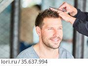 Mann bekommt einen Haarschnitt mit der Schere beim Friseur oder zu... Стоковое фото, фотограф Zoonar.com/Robert Kneschke / age Fotostock / Фотобанк Лори