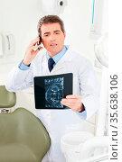 Zahnarzt telefoniert mit Röntgenbild von einem Gebiss in der Hand. Стоковое фото, фотограф Zoonar.com/Robert Kneschke / age Fotostock / Фотобанк Лори