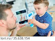 Vater und Kind mit Fieberthermometer in der Online Sprechstunde am... Стоковое фото, фотограф Zoonar.com/Robert Kneschke / age Fotostock / Фотобанк Лори
