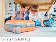 Kind mit einem Koffer spielt Verreisen im Wohnzimmer auf dem Fußboden. Стоковое фото, фотограф Zoonar.com/Robert Kneschke / age Fotostock / Фотобанк Лори