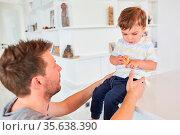 Vater kümmert sich fürsorglich um seinen Sohn beim Keks essen zu Hause. Стоковое фото, фотограф Zoonar.com/Robert Kneschke / age Fotostock / Фотобанк Лори