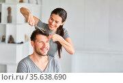 Junges Paar beim Haare selber schneiden zu Hause mit Kamm und Schere. Стоковое фото, фотограф Zoonar.com/Robert Kneschke / age Fotostock / Фотобанк Лори