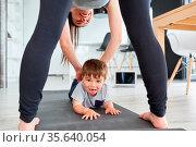 Mutter hilft Kind beim spielen und turnen auf der Gymnastikmatte ... Стоковое фото, фотограф Zoonar.com/Robert Kneschke / age Fotostock / Фотобанк Лори