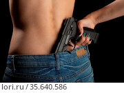 Female body with gun inside her jeans, black background. Стоковое фото, фотограф Zoonar.com/A.Tugolukov / easy Fotostock / Фотобанк Лори