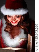 Christmas. happy girl in Santa hat opening glowing magic surprise... Стоковое фото, фотограф Zoonar.com/Ivan Mikhaylov / easy Fotostock / Фотобанк Лори