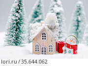 Small decorative snowman with gift near wooden house in fir forest... Стоковое фото, фотограф Zoonar.com/Ivan Mikhaylov / easy Fotostock / Фотобанк Лори