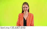 Happy positive woman laughing in space studio on yellow background. Стоковое видео, видеограф Gennadiy Poznyakov / Фотобанк Лори