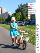 Unhappy preschool girl carrying her bicycle on asphalt lane holding steering wheel. Стоковое фото, фотограф Кекяляйнен Андрей / Фотобанк Лори