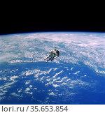 NASA Astronaut Robert L. Stewart Floats Above Cloudy Earth During... Редакционное фото, агентство World History Archive / Фотобанк Лори