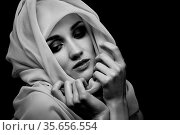 Beautiful young woman with white headscarf cover her face with luxury... Стоковое фото, фотограф Zoonar.com/A.Tugolukov / easy Fotostock / Фотобанк Лори
